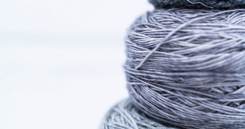 Image of three stacked blue/grey yarn cakes by Les Triconautes on Unsplash