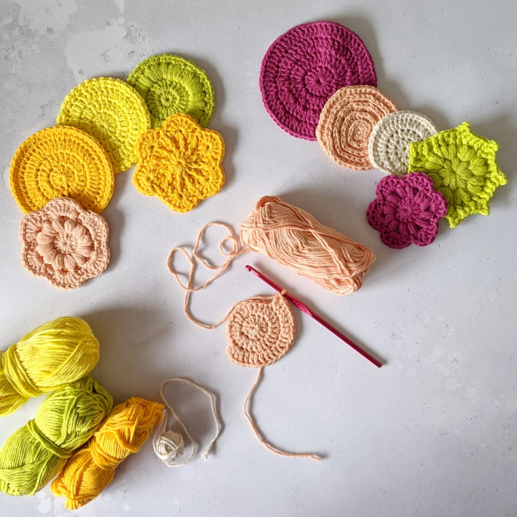 Ten finished crochet face scrubs in round and flower shapes made in yellow, green, peach and pink yarn. There is also a face scrub in progress