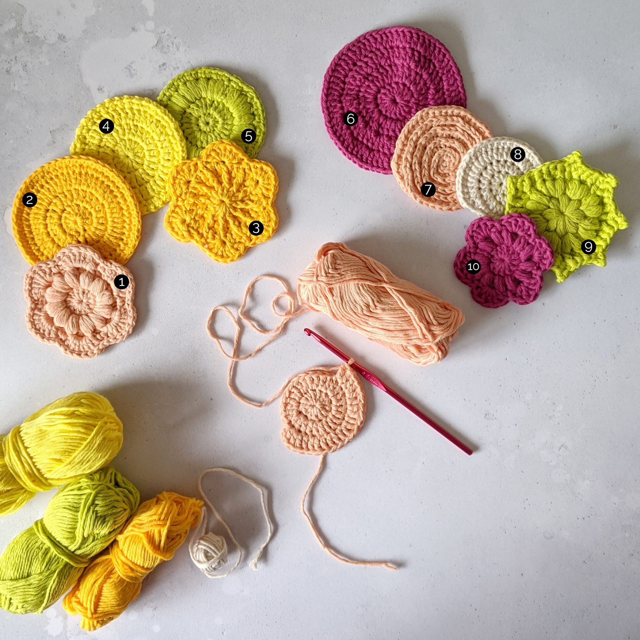Ten finished crochet face scrubs in round and flower shapes made in yellow, green, peach and pink yarn. There is also a face scrub in progress. Marked up with numbers 1- 10