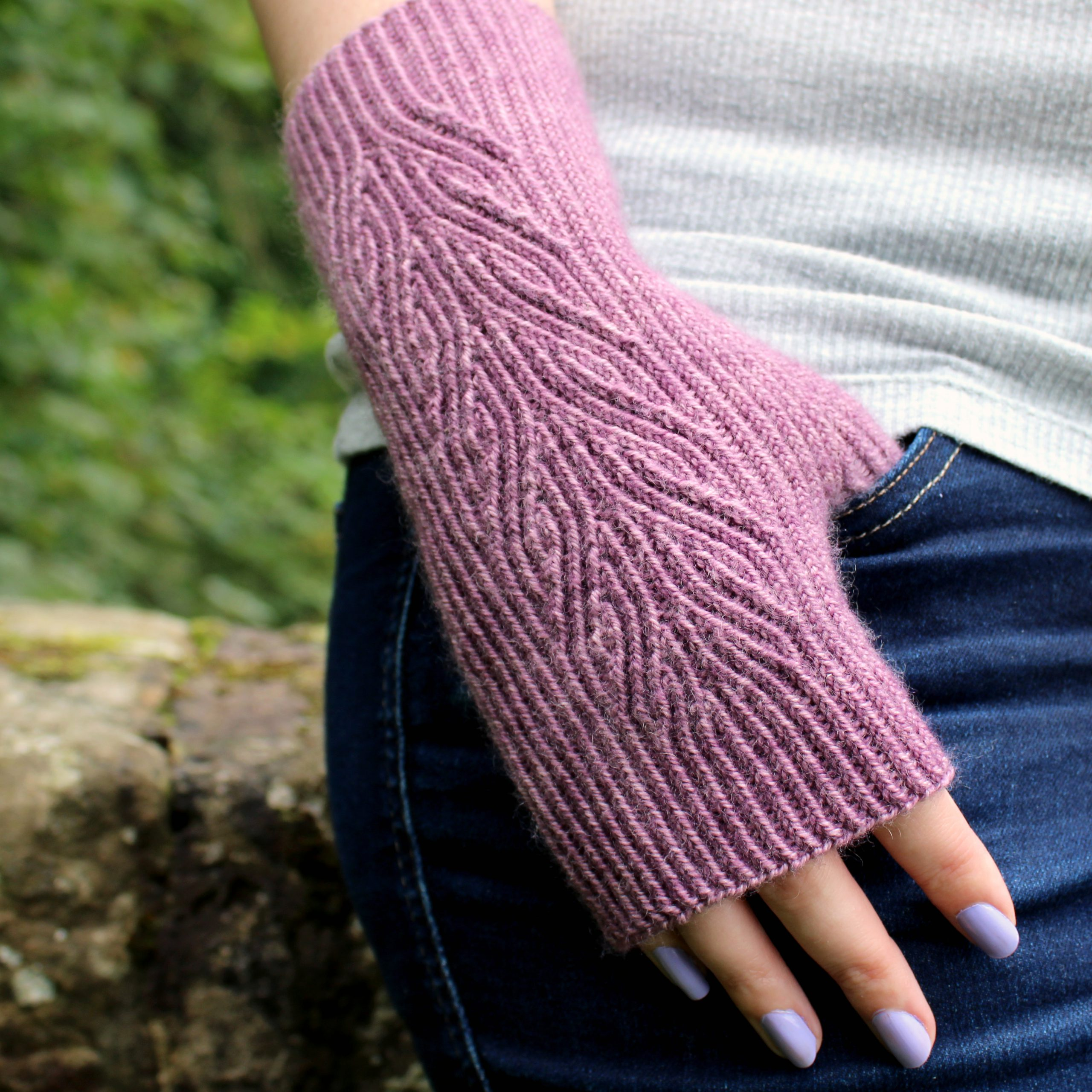 A purple fingerless mitt with a flowing faux cable pattern.