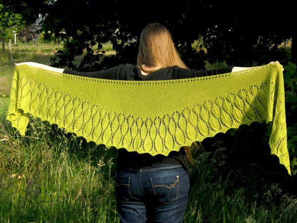 A green shawl with a feather patterned border spread to show the shallow crescent shape