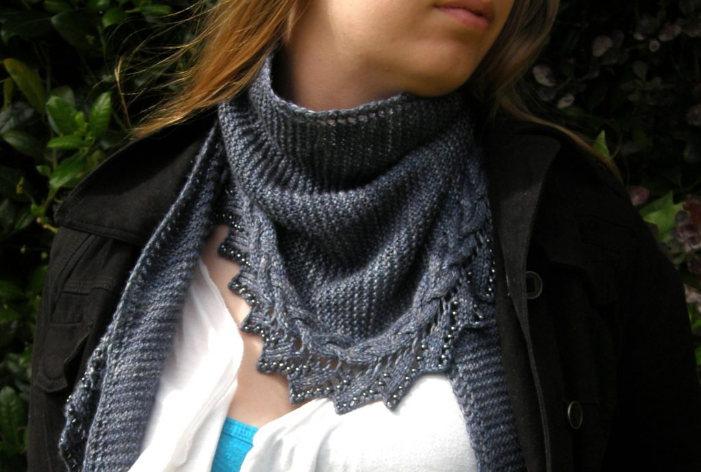 A shawl with a cabled, lace and beaded edge