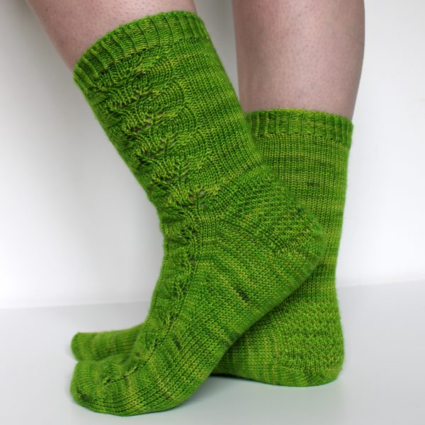Green socks with a lace leaf pattern up the outside of the foot and leg