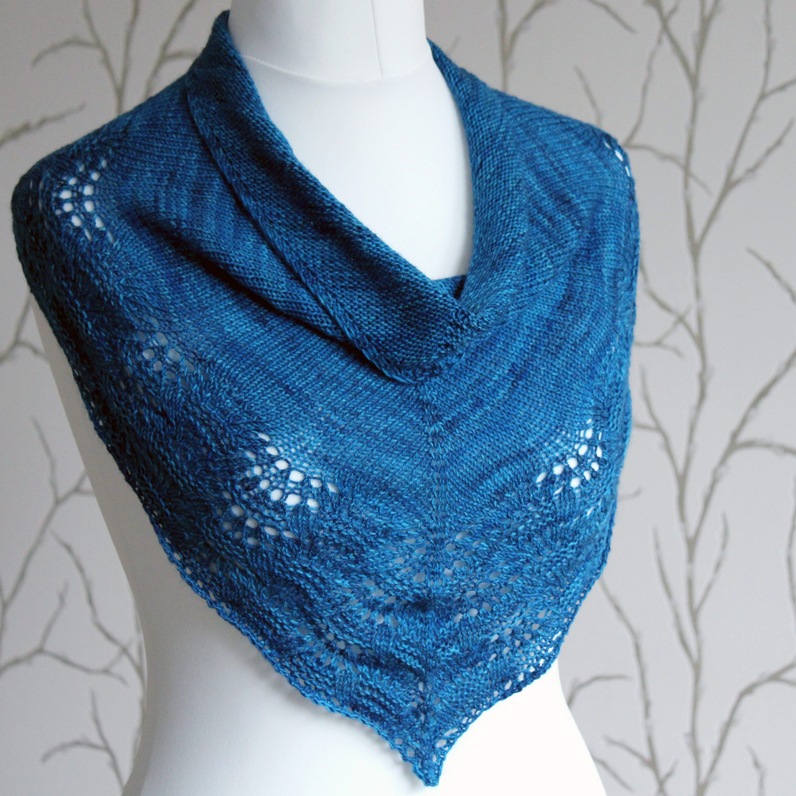 A blue triangular cowlette with a stocking stitch body and rippling lace and textured border
