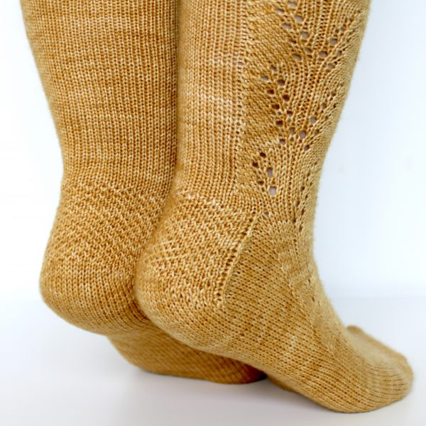 Golden socks with a lace wheat pattern up the outside of the foot and doubling at the leg