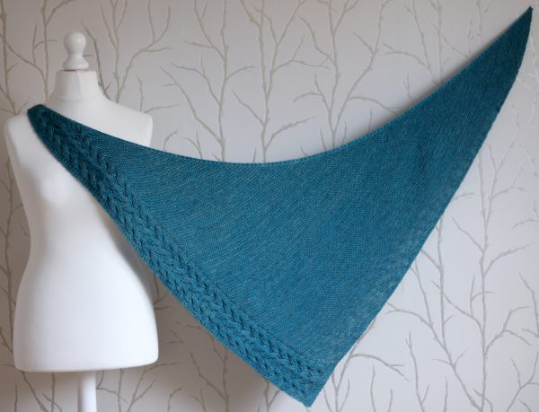 A blue garter stitch shawl with a rippling cable pattern down one side stretched to show the shape