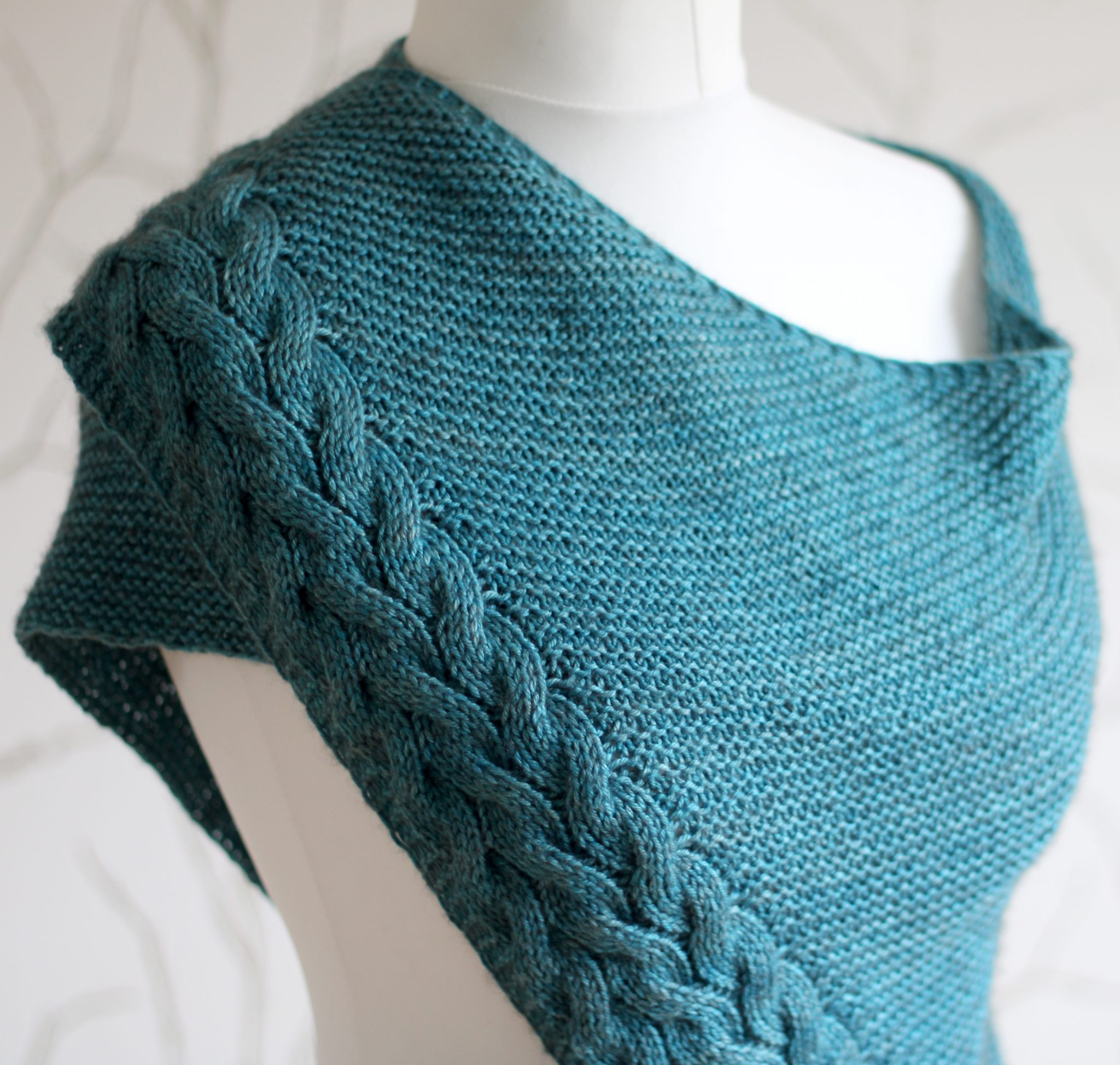 A blue garter stitch shawl with a rippling cable pattern down one side wrapped around a mannequin