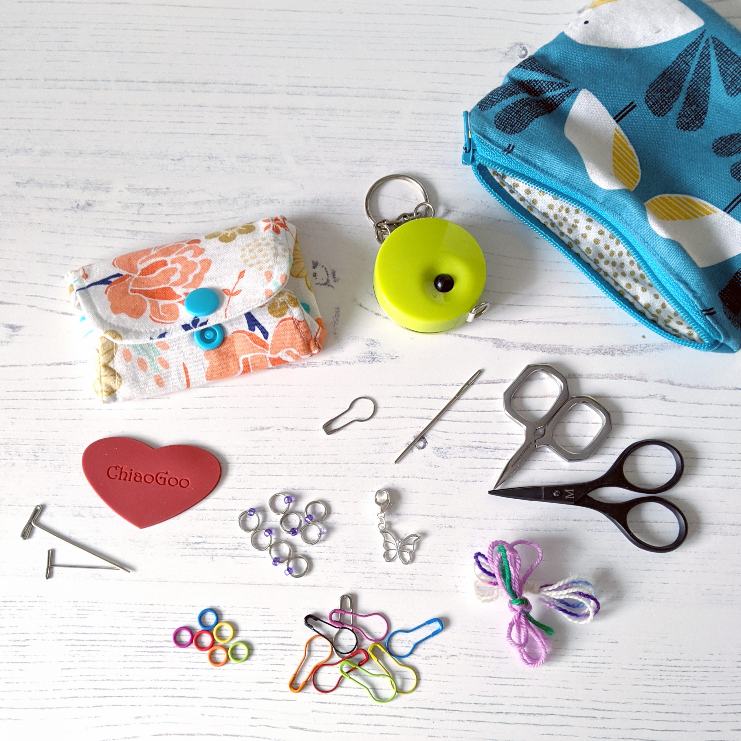 Notions pouches, tape measure, scissors, scrap yarn and a selection of stitch markers