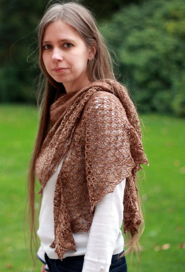 A crescent shawl with a stockinette body and wide lace section