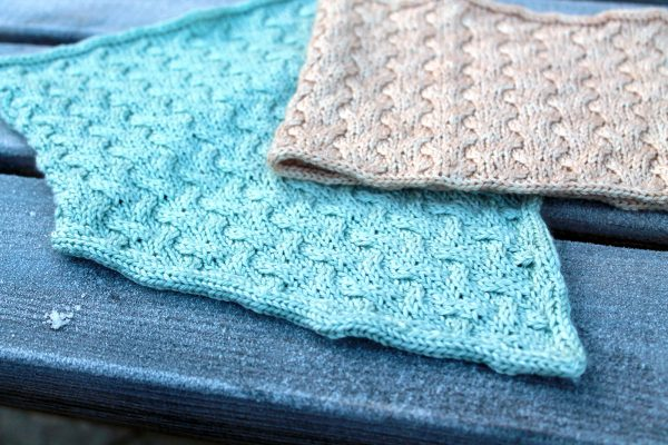 A close up of two cowls with cables and i-cord edging. one has a straight bottom edge and one has a pointed edge
