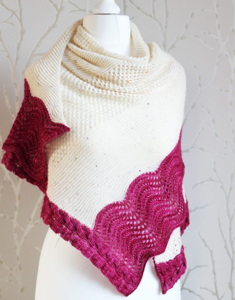 A white triangular shawl with lace and garter stitch stripes and a pink intarsia cable down the side and wavey pink border