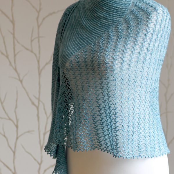 A crescent shaped shawl with a central lace mesh panel and two garter stitch sections