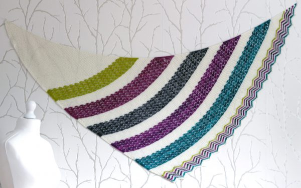 A shawl with coloured lace stripes and chevron border showing the triangular shape