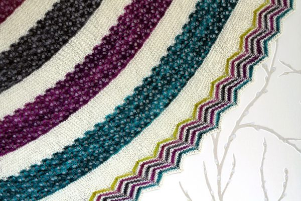 A shawl with coloured lace stripes and chevron border