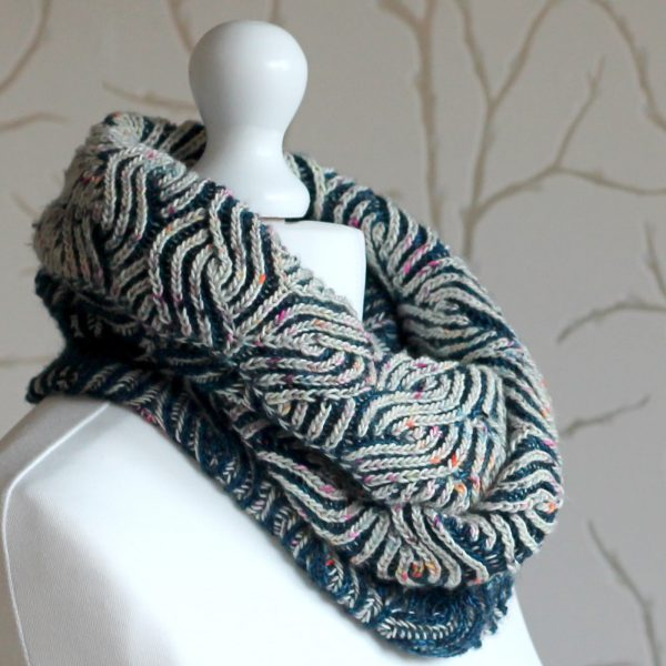 A mannequin displaying a long brioche cowl in blue and white with a owl pattern wrapped twice around the neck