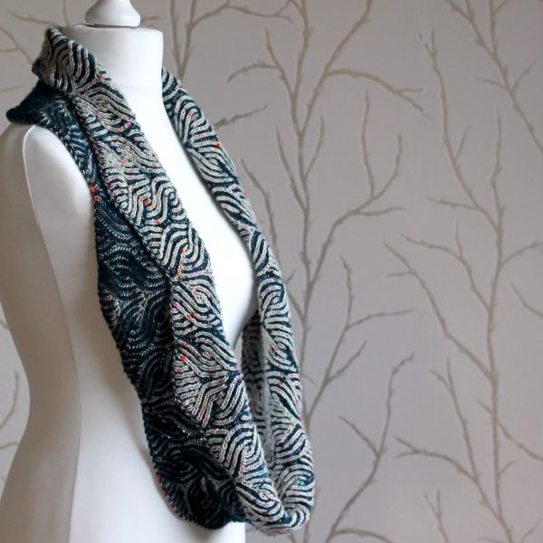A mannequin displaying a long brioche cowl in blue and white with a owl pattern