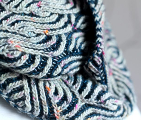 A close up on a long brioche cowl wrapped twice around a mannequin