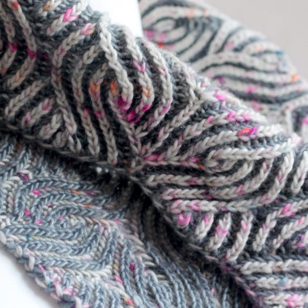 A close up on a brioche cowl showing the owl pattern