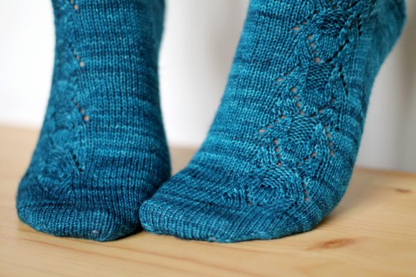 Blue socks with a column of lace up the outside of the foot