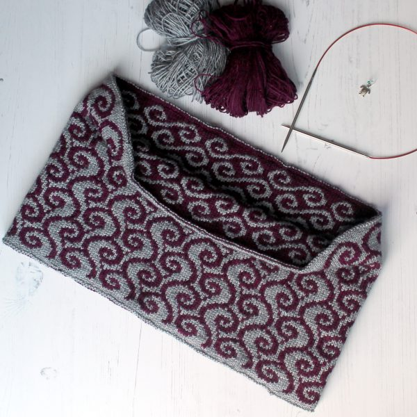 A colourwork cowl with purple waves against a grey background on the outside and grey swirls against a purple background on the inside