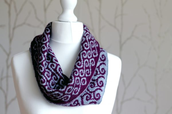 A colourwork cowl with purple waves against a grey background on the outside and grey swirls against a purple background on the inside which has been folded down