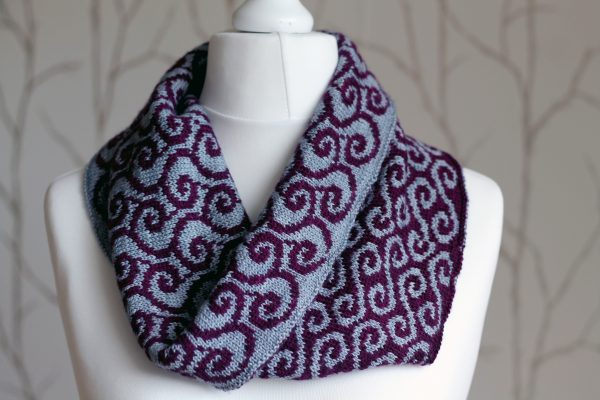 A colourwork cowl with grey swirls against a purple background on the outside and purple waves against a grey background on the inside which has been folded down