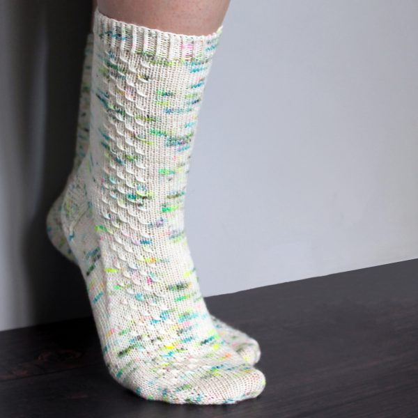 A pair of speckled socks with a column of textured pattern up the outside of the foot