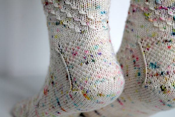 A close up on the heels of speckled pair of socks with a textured chevron pattern