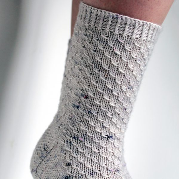 Grey speckled socks with an all-over textured pattern mirrored on each foot
