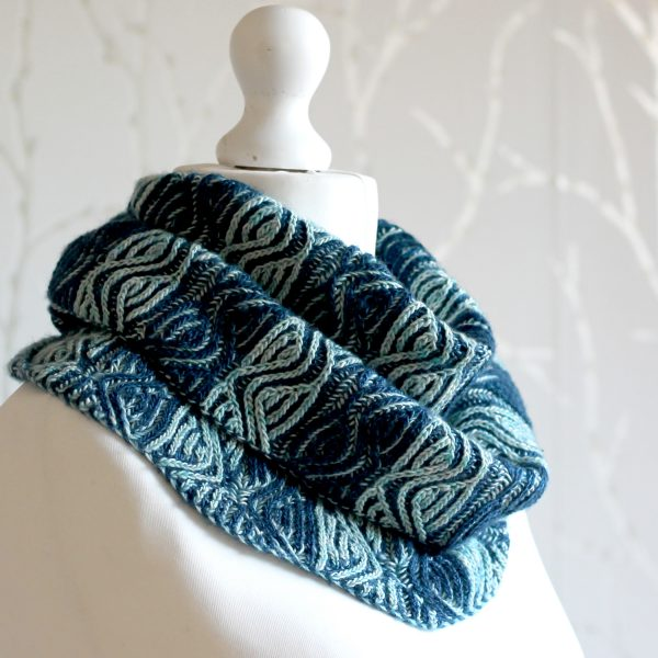 A mannequin displaying a long brioche cowl with dark and light blue vertical stripes and a faux cable pattern wrapped twice around the neck