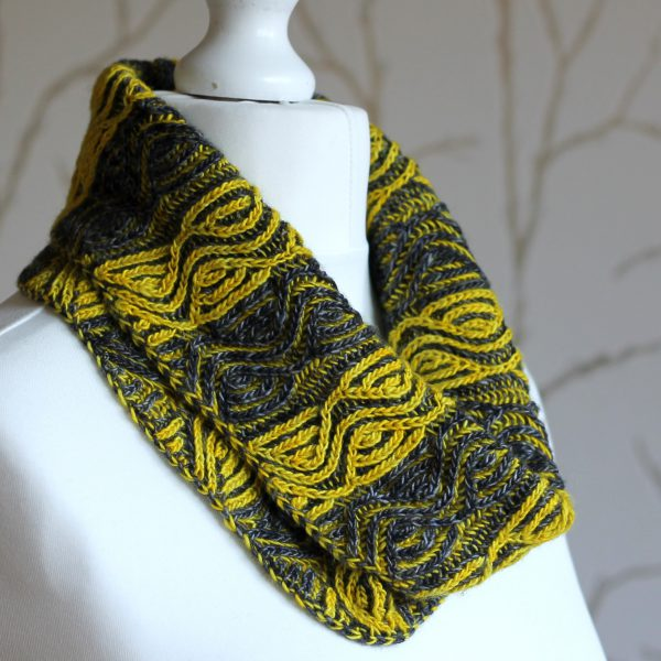 A mannequin displaying a short brioche cowl with grey and yellow vertical stripes and a faux cable pattern