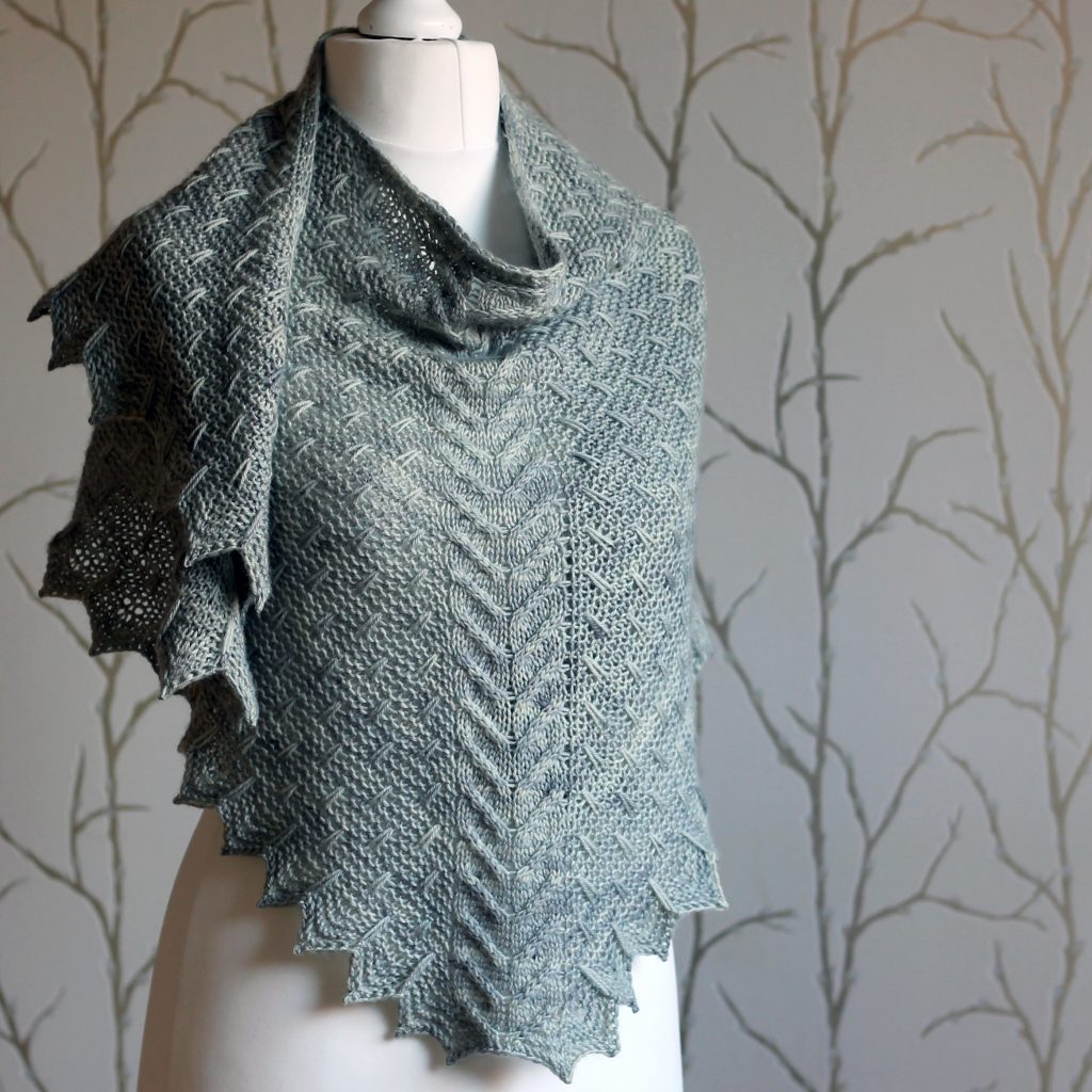 A grey shawl with a cabled spine, a garter stitch body with slipped stitch detail and chevron detail on the edge.