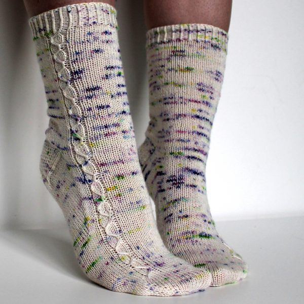 Speckled socks with a slipped stitch cable pattern up the outside of the foot