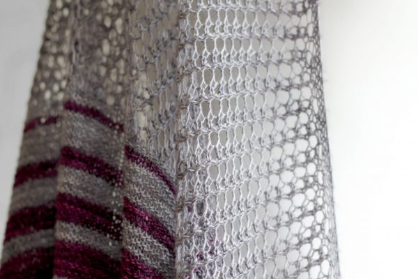 A close up on the lace section of purple and grey striped shawl with lace panels draped around a mannequin
