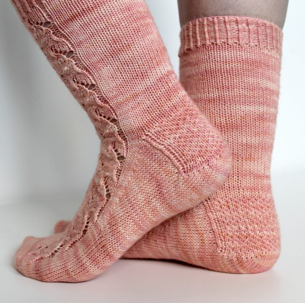Pink socks with a floral pattern up the outside of the foot and leg