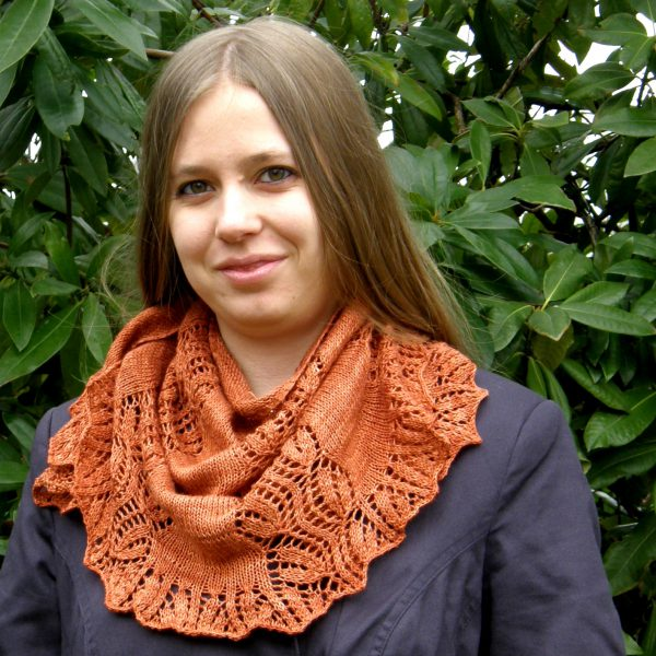 A crescent shawl with a lace vine pattern climbing up towards the top