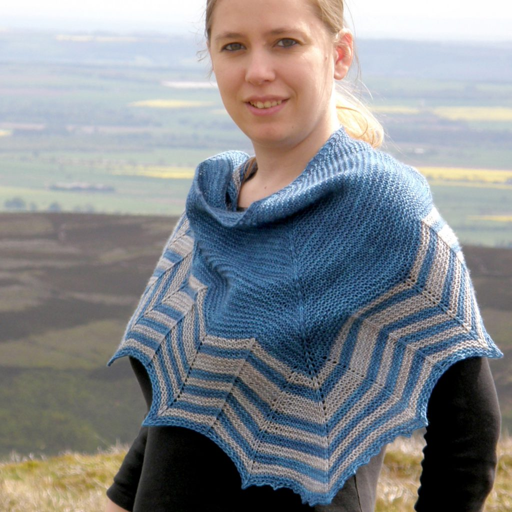 A triangular shaped shawl with a striped chevron edge