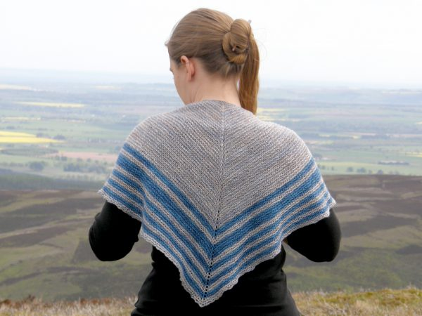 A triangular shaped shawl with a smooth striped edge