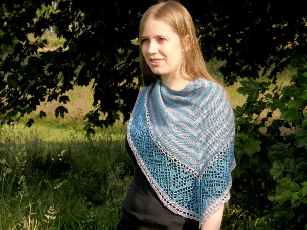 A triangular shawl with a striped stockinette body and a wide lace panel