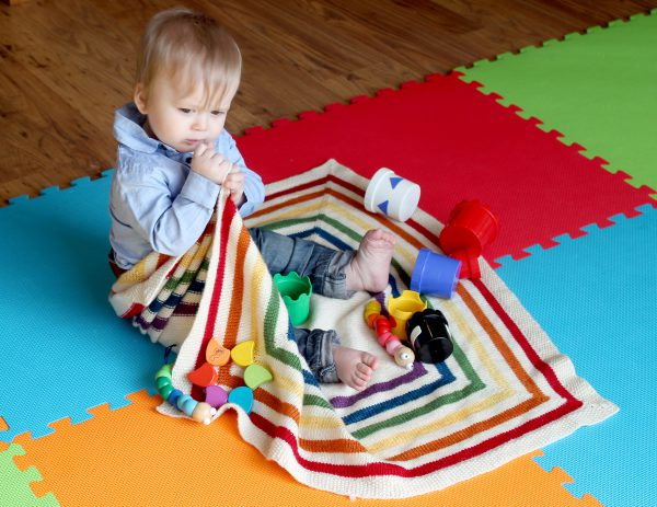 A square baby blanket with rainbow stripes and a seed stitch border