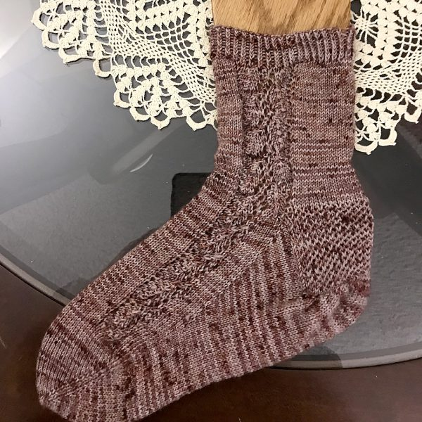A sock with a lace leaf pattern up the outside of the foot knitted in variegated brown yarn