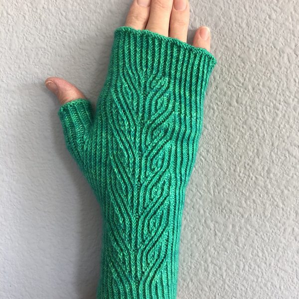 A green fingerless mitt with twisted rib and a faux cable pattern, against a white wall