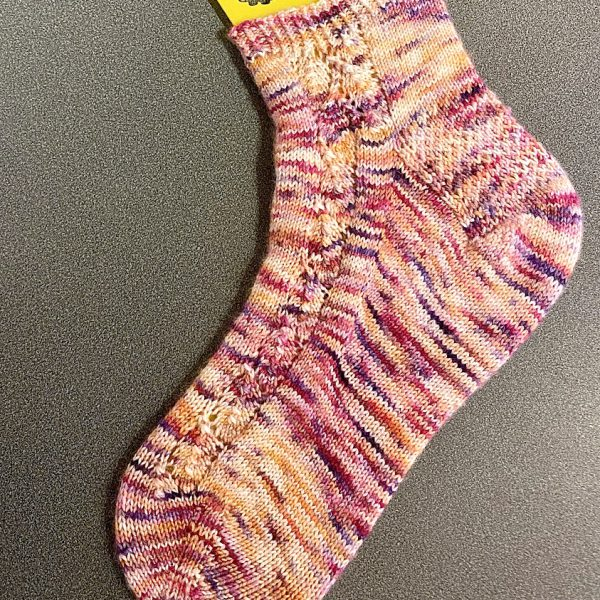A sock with a lace leaf pattern up the outside of the foot knitted in variegated pink yarn
