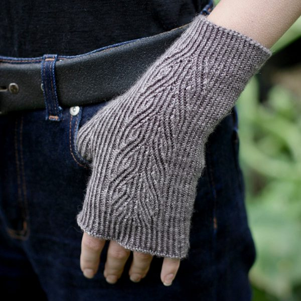 A twisted rib fingerless mitt with a sweeping faux cable pattern up the back of the hand in grey yarn, with the thumb caught in the pocket of the wearer
