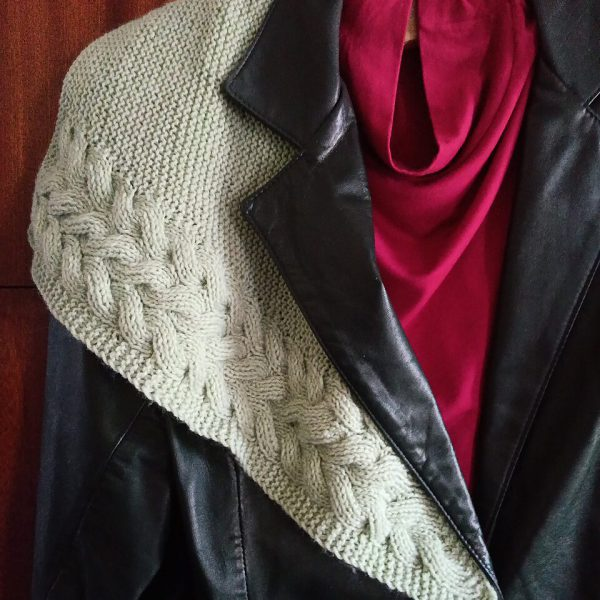 A white cabled shawl draped over a jacket