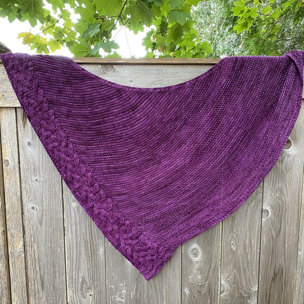 An asymmetrical garter stitch shawl with a reversible cable pattern down one edge hanging over a fence