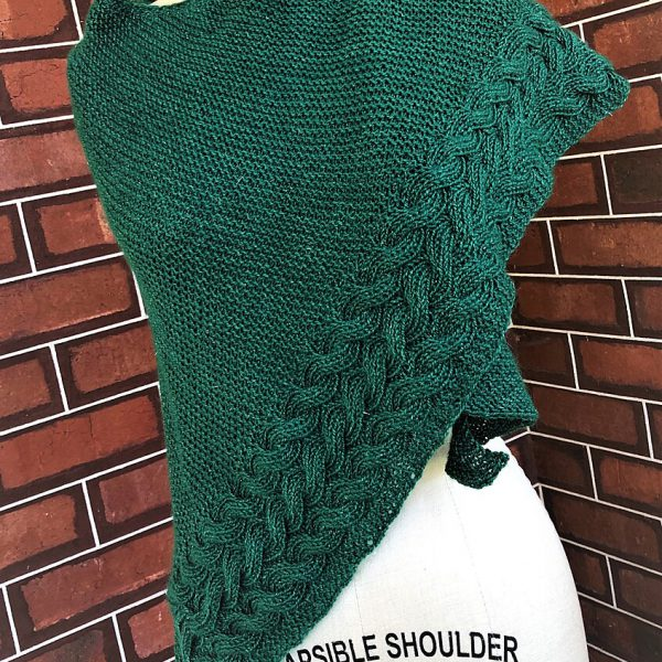 A green triangular cabled shawl draped over a mannequin