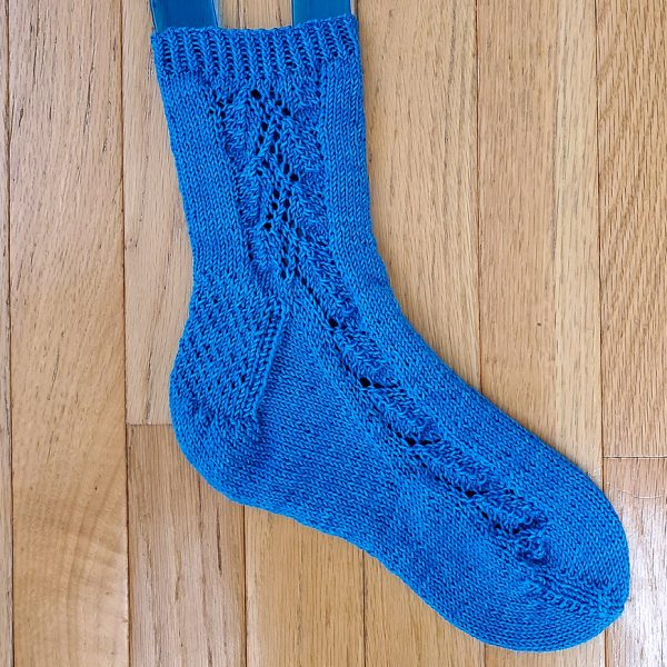 An blue sock with a lace leaf pattern up the outside of the foot
