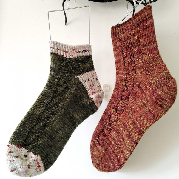 Two socks with a lace leaf pattern up the outside of the foot knitted in variegated brown yarn and green yarn with contrast toe, heel and cuff.