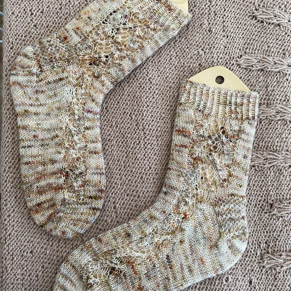 A pair of socks with a lace leaf pattern up the outside of the foot knitted in speckled cream and brown yarn